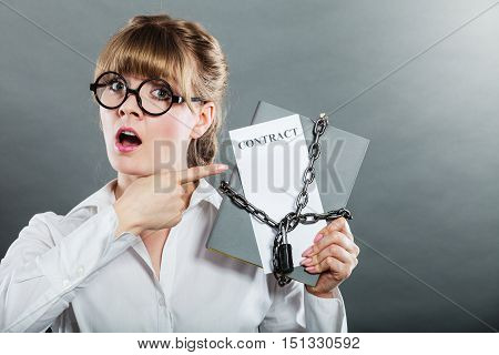 Business concept limited by contract. Woman holding in hands paper document chained with padlock