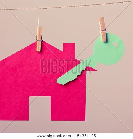 Red house with green key hang on laundry line on background. Selling and buying home concept.
