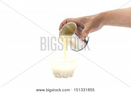 Man hand pouring condensed milk into a bowl isolated