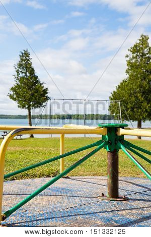 sunny summer day at Berford Lake park. An empty roundabout in forground with swing set overlooking the lake.