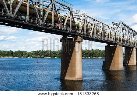 Petrivskiy railroad bridge in Kyiv across the Dnieper with freight train on it.