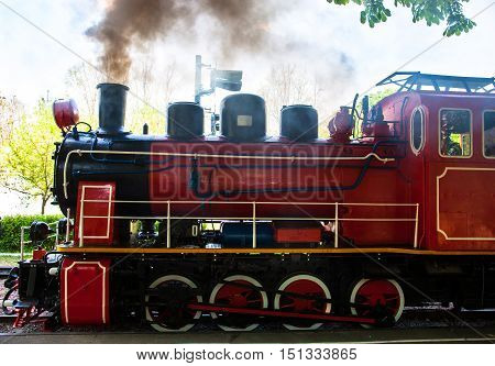 Steam locomotive with the smoke blowing off out of the smokestack.