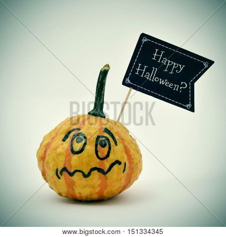 closeup of a terrified pumpkin with a black flag-shaped signboard with the question Happy Halloween? written in it, against an off-white background