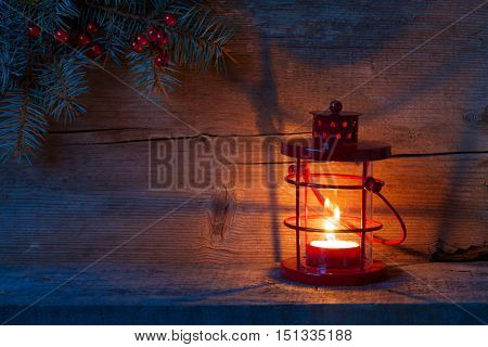 Christmas lantern in dusk on old wooden background.