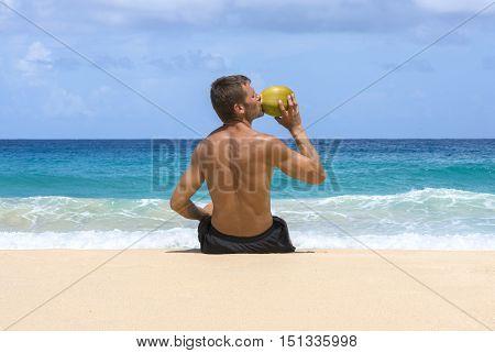 Tan shirtless Caucasian man sitting on deserted Caribbean beach drinking water from fresh coconut under bright sunshine