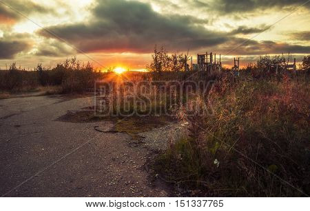 The setting sun illuminates the old ruins overgrown with grass
