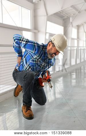 Hispanic worker suffering back injury inside building