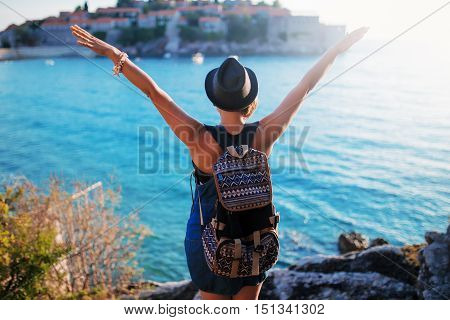 Woman Traveler With Backpack Near Sveti Stefan At Adriatic Sea, Hands Up In The Air