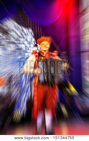 Musician playing the accordion on stage Opera mask theater gold. Abstract blur zoom.