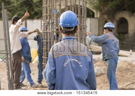 Tehran IRAN - June 6 2016 Construction Workers Putting Cylindrical Metal Structure in Place