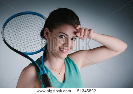 Young Woman Tired After Playing Tennis With Racket Over Her Shoulders Wiping The Sweat From Her Fore