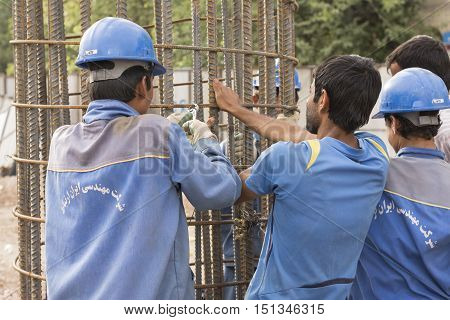 Tehran IRAN - June 6 2016 Construction Workers Working on Cylindrical Metal Structure