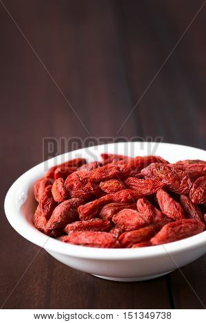 Dried gojis or wolfberries in small bowl photographed on dark wood with natural light (Selective Focus Focus one third into the image)