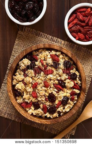 Crunchy oatmeal cereal with almond and dried goji berries and cranberries in wooden bowl photographed overhead on dark wood with natural light (Selective Focus Focus on the top of the cereal and the berries)