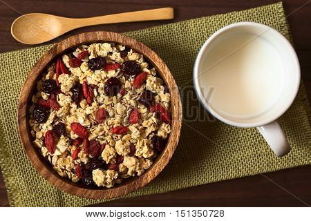 Crunchy oatmeal cereal with almond and dried goji berries and cranberries in wooden bowl with a cup of milk on the side photographed overhead with natural light (Selective Focus Focus on the top of the cereal)