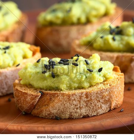 Bread slices with green pea and parsley spread garnished with black sesame seeds served on wooden plate photographed with natural light (Selective Focus Focus on the front of the spread on the first bread)
