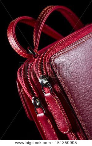 Red leather bag with zipper, shoulder strap and stitches, woman's accessories, fashion industry, selective focus