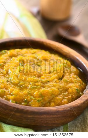 Pumpkin and parsley puree in wooden bowl photographed with natural light (Selective Focus Focus one third into the puree)