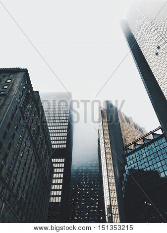 dense fog above city skyscraper tower buildings