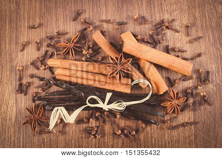 Vintage Photo, Vanilla, Cinnamon Sticks, Star Anise And Cloves On Wooden Surface