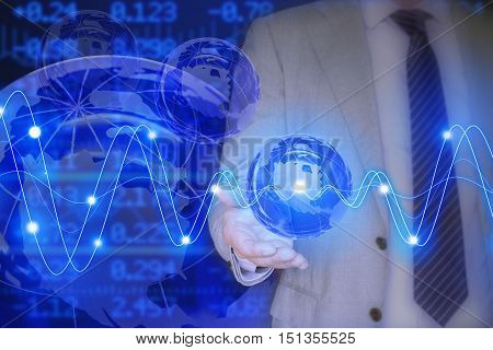 Businessman in a grey suit holding a glass globe in front of a stock ticker wall with glowing waves global business concept
