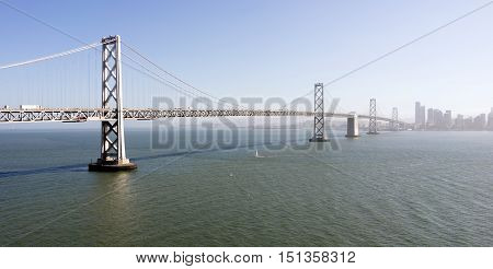 Vehicles and boats move along above and below the Bay Brdige in San Francisco