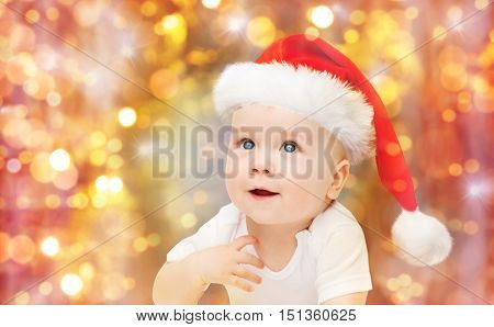 childhood, christmas, holidays and people concept - beautiful little baby boy in christmas santa hat over lights background