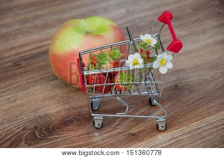 Small shopping cart with strawberries near big apple on wooden background. Top view