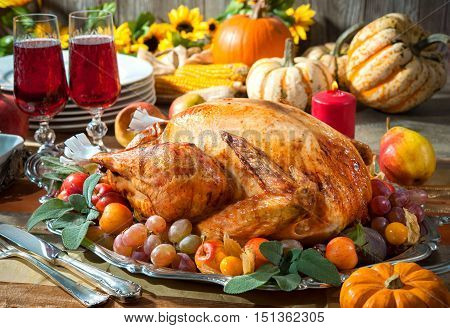 Thanksgiving dinner. Roasted turkey on holiday table with pumpkins flowers and wine