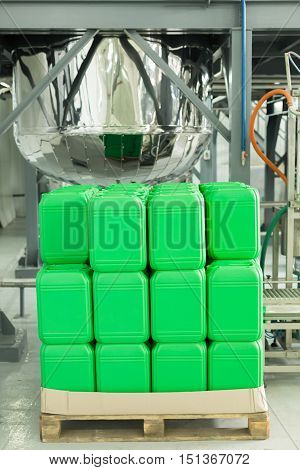 Wooden Pallet With Plastic Green Color Cans.