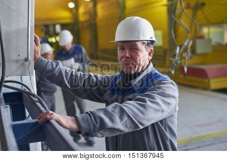Portrait of male worker in overalls and helmet presses a button on the control panel equipment at the plant
