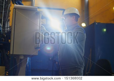Male worker in overalls and helmet presses on the control panel of the equipment in the factory