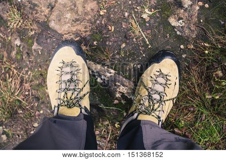 Hiker shoes on dirt autumn footpath in forest on hiking trip. Legs and hiking boots on trail background closeup. Travel recreation fitness and healthy lifestyle concept outdoors in nature.
