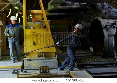 Worker in hard hat and overalls, and pulls the rope with a hook in the premises of the plant