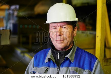 Portrait of a Builder in overalls and helmet in the premises of the plant