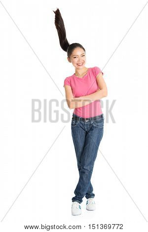 Portrait of young Asian woman in pink shirt and jeans with flying ponytail hair, full length standing isolated on white background.
