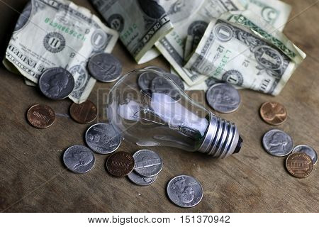 coins and crumpled money tungsten lamp filament