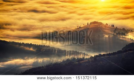 Sunrise landscape of foggy and cloudy mountain valley. Majestic sunrise