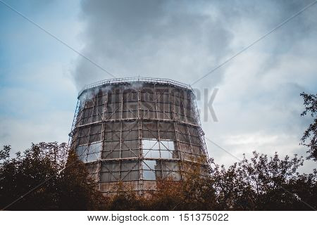 big old cooling pipe with steam smoke in cloudy weather in autumn