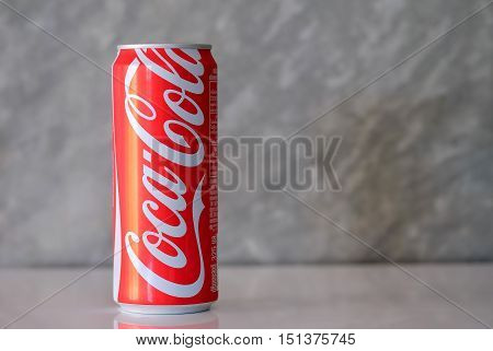 CHIANGMAITHAILAND - October 11 2016: Can of Coca Cola place on white floor with concrete wall background close-up. Coca-Cola Company is the leading manufacturer.
