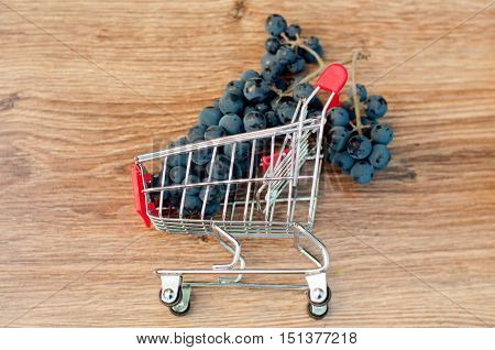 Bunch of blue grapes in small metal shopping cart laying on brown wooden table. Top view