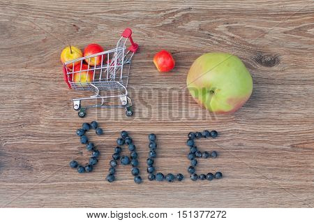 Word sale made of blue grape berries small shopping cart and different size apples laying on brown wooden table