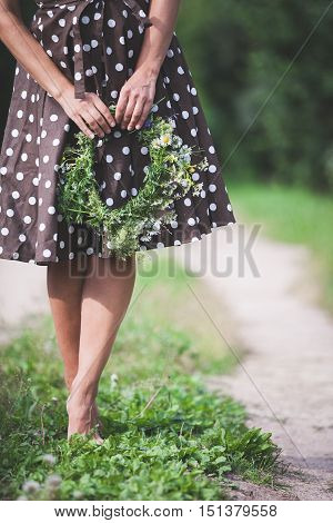 Closeup of woman's hands holding floral wreath. Woman in dotted dress holding wild flowers wreath and standing on a road. Summertime and lifestyle concept.
