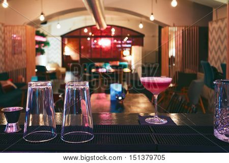 Interior of the small night bar in downtown. Red coctail on the bar counter - selective focus on the drink