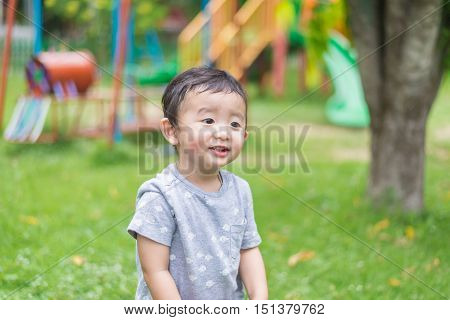 Little Asian Kid Playing And Smiling At The Playground Under The Sunlight In Summer, Shallow Dof