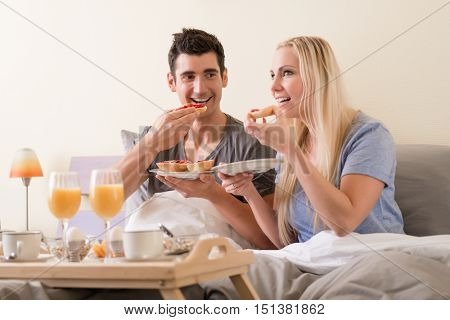 Young couple celebrating with breakfast in bed sitting eating berry jam o toast accompanied by fresh orange juice and boiled eggs