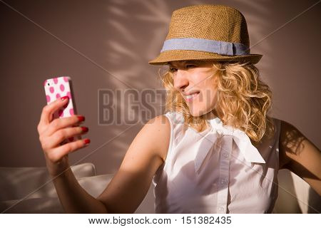 Portrait of smiling young woman in straw hat taking selfie with her smartphone. Girl taking picture with phone.