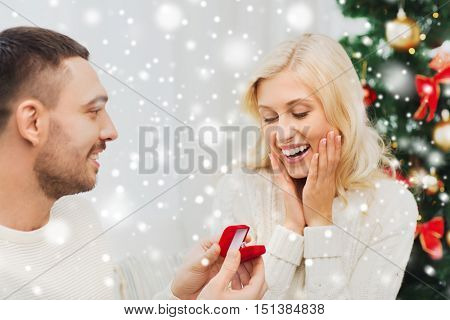 love, christmas, couple, proposal and people concept - happy man giving diamond engagement ring in little red box to woman at home
