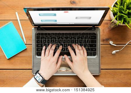 online communication, business, people and technology concept - close up of woman or student typing on laptop computer with messenger or internet chat on screen, notebook and earphones on wooden table