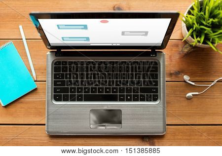 online communication, education, business and technology concept - close up of laptop computer with messenger or internet chat on screen on wooden table